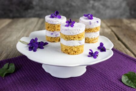 focus on violet flower small cakes with mascarpone violaceous cream on ceramic whatnot