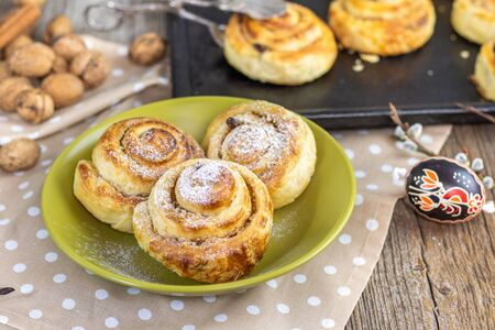 easter sweet croissant brioche snail with raisin-walnut filling on green plate Stock Photo