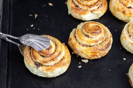sweet croissant brioche snail with raisin-walnut filling with confectionery tongs on black baking tray