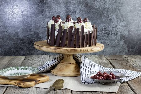 traditional schwarzwald cake with bowl with cherries set on old table