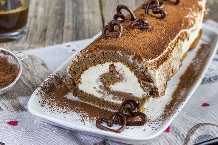 detail on a tiramisu roulade on white cocoa tray with dark chocolate hearts