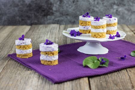 violet flower small cakes with mascarpone violaceous cream set on old wood table