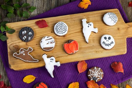 Handmade halloween cookies on a wooden board from above