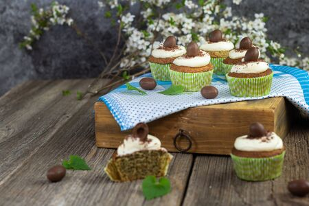 nettle cupcake with mascarpone and white chocolate cream and chocolate easter egg set on old wood table