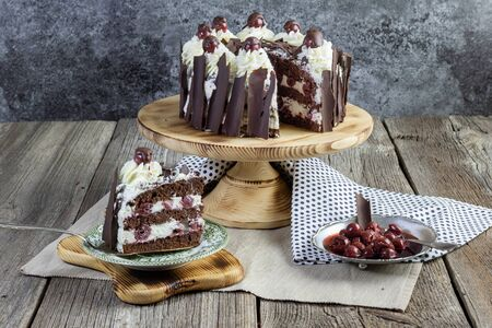 traditional schwarzwald cake with slice of cake set on old table