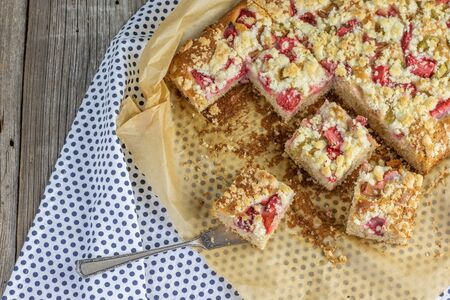 strawberry rhubarb crumble cake on blue brindle plate on a baking paper Stock Photo