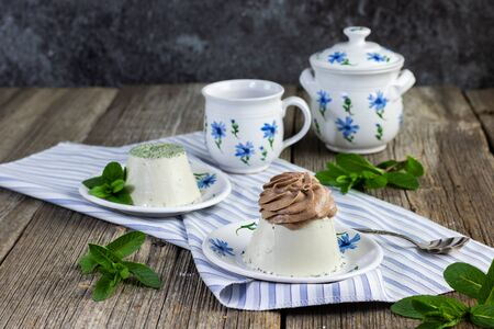 mint panna cotta with chocolate cream set on a old table