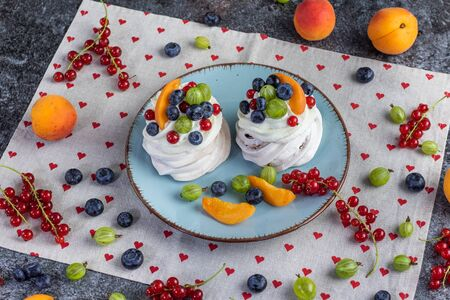 mini pavlovs with garden fruits (currants, gooseberries, blueberries, apricots) on a table full of fruits from above