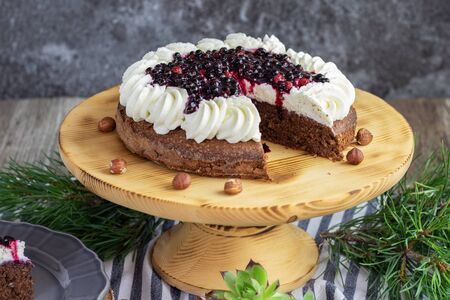 detailed view on a forest chocolate hazelnut cake with wild strawberries, blueberries, raspberries and blackberries garnished with whipped cream