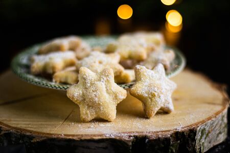 Christmas vanilla star biscuit (christmas sweets ) witch christmas light on a wooden log Stock Photo