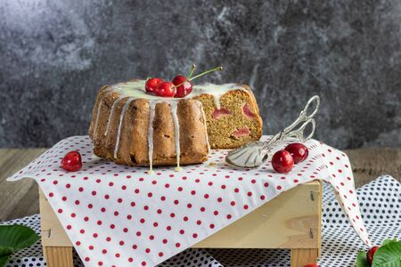 curd cheries cake with lemon topping with confectionery tongs on tablecloth with red polka dots Stock Photo
