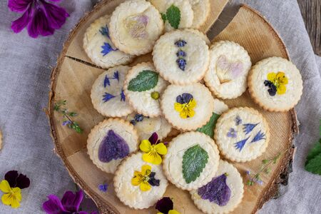 top view on almond floral cookies with edible flowers as violets, speedwell, chamomile, mallow or lemon balm and mint leaves