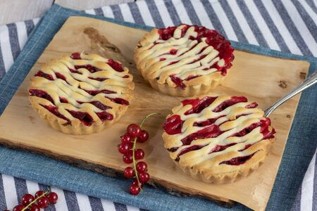 shortcrust red currant tartlets with sour currant filling on rustic wooden cutting board