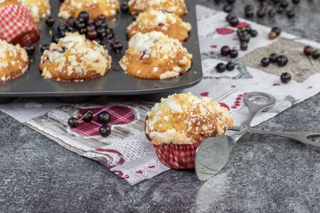 confectionery tongs with black currant muffin with crumb on a marble desk