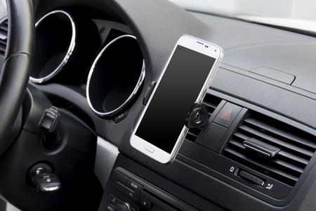 White smartphone docked on a car dashboard Foto de archivo