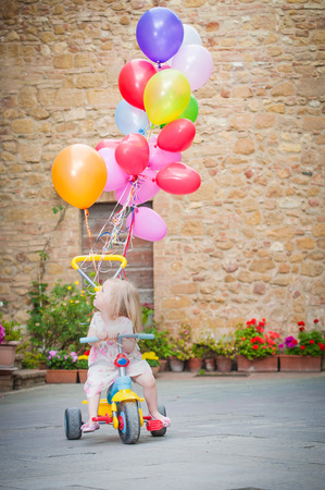 Little girl on tricycle with balloons photo