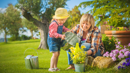 Little girl helping her mother in the garden photo
