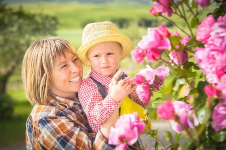 Woman and daughter doing garden work in summer sunny day photo