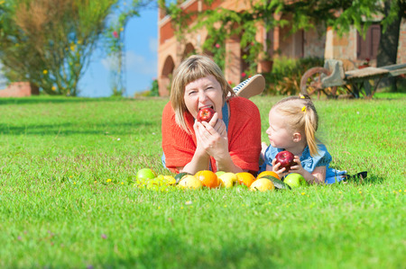 Mother and daughter eating the colorful fruit on green grass photo
