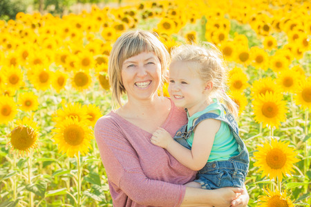 Mother and daughter among sunflowers having fun photo