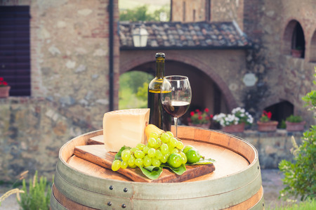 Red wine, pecorino cheese, grapes, bottle and glass on wooden barrel in the background of the Tuscan landscape, Italy Standard-Bild