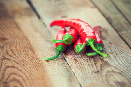 red chilli pepper plant: Very spicy peppers, chili, cayenne, jalapeno, peperoncino on wooden background Stock Photo