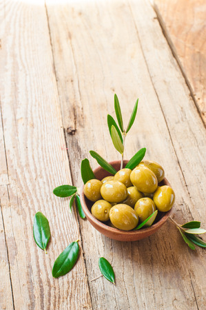 Olives on rustic table in a bowl photo