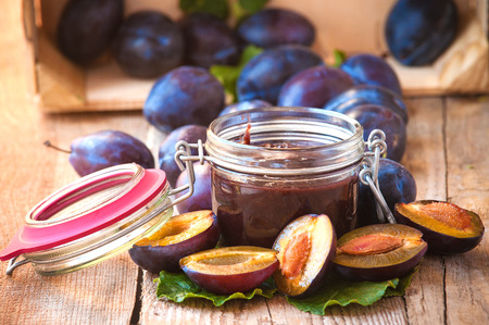 Jar of plum jam surrounded by plums on background wooden rural table Standard-Bild