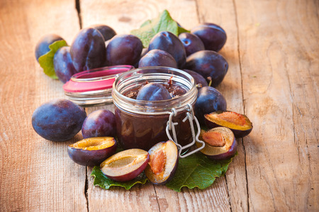 Jar of plum jam surrounded by plums on background wooden rural table photo