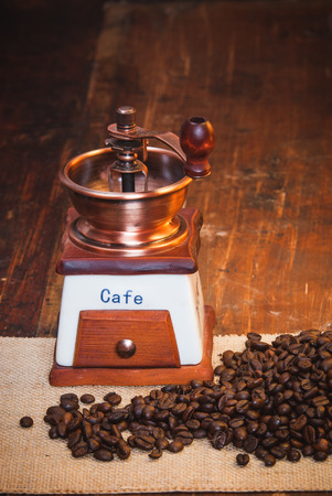 Coffee grinder with coffee grains on a wooden rustic table photo