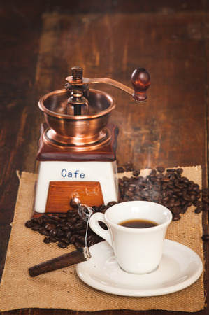 Cup of black coffee and a cigar in the background grinder on a wooden rustic table photo