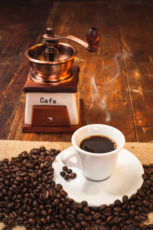 Cup of black coffee in the background grinder on a wooden rustic table photo