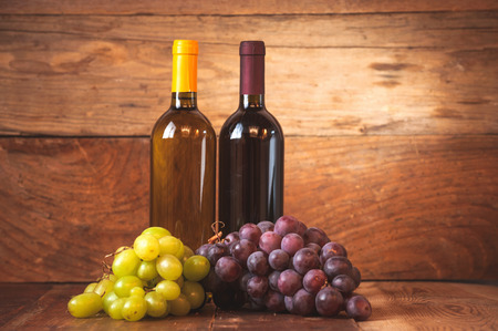 Red and white wine bottle with grapes on wooden rustic table. photo