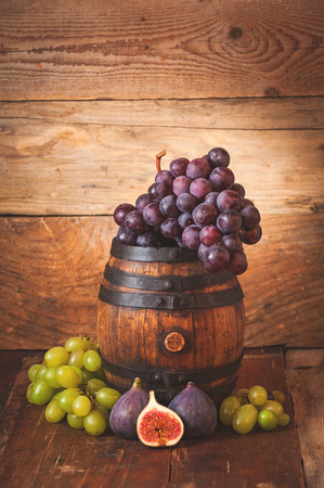 Red and white grapes on a rural wooden barrel photo