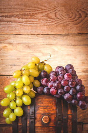 Red and white grapes on a rural wooden barrel
