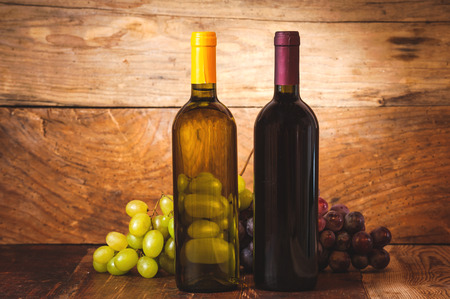 Red and white wine bottles with grapes and barrel on wooden rustic table. photo
