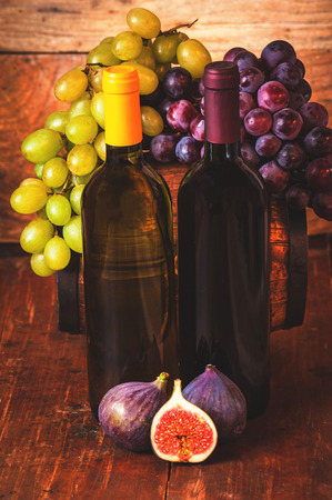 Red and white wine bottle with grapes and barrel on wooden rustic table. photo