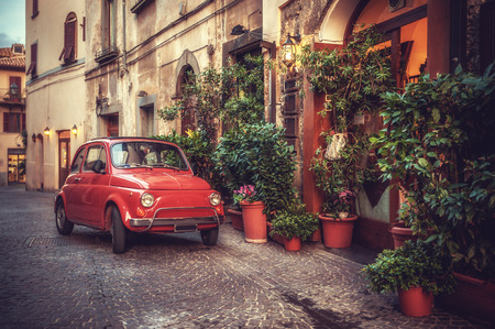 Old vintage cult car parked on the street by the restaurant, in the Italian town. Foto de archivo