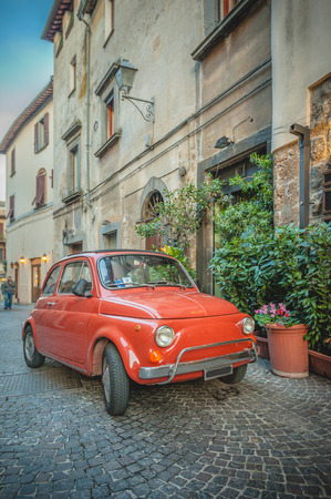 Old vintage cult car parked on the street by the restaurant, in the Italian town. Archivio Fotografico