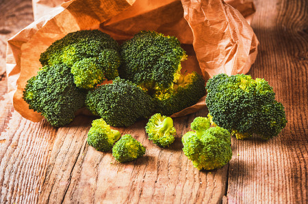 Green delicious broccoli on a wooden rustic table photo