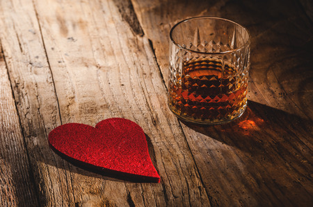 Heart and a glass of alcohol on a wooden table in the bar photo
