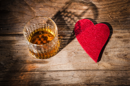 Heart and a glass of alcohol on a wooden table in the bar