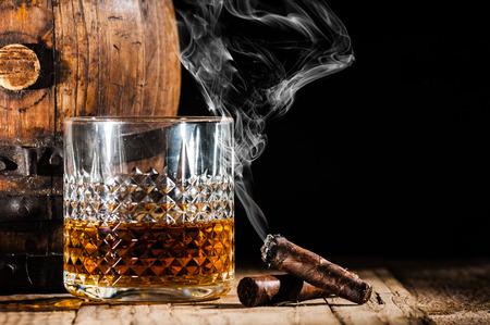 Glas alcohol en roken nobele sigaar op een zwarte achtergrond
