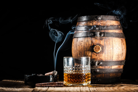 cigar: Glass of alcohol and smoking noble cigar on a black background