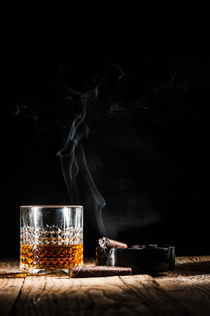 drunks: Glass of alcohol and smoking noble cigar on a black background