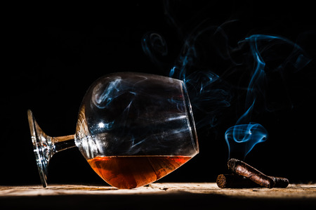 Glass of alcohol and smoking noble cigar on a black background Фото со стока - 34912402