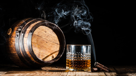 drunks: Glass of alcohol and smoking cigar on a black background noble