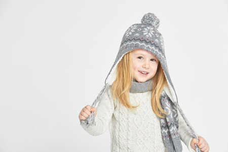 Beautiful blond girl playing in the winter warm hat and scarf on a white background