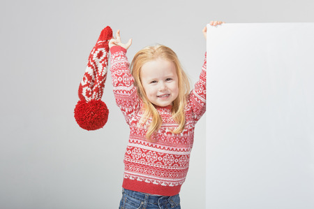 Smiling beautiful blond girl in a red winter cap and sweater with white space for text or advertisement photo