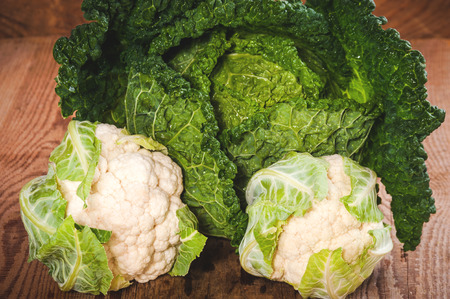 Savoy cabbage and cauliflower on a wooden rustic table photo